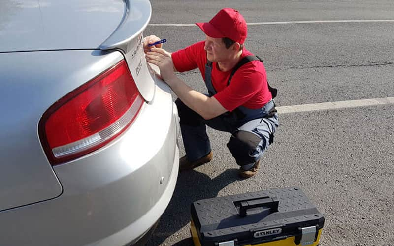 мастер открывает багажник авто